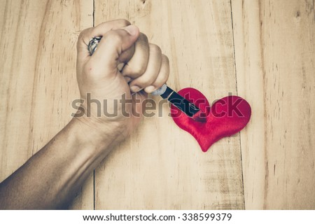 hand with a knife stabbing into a red heart  - stock photo