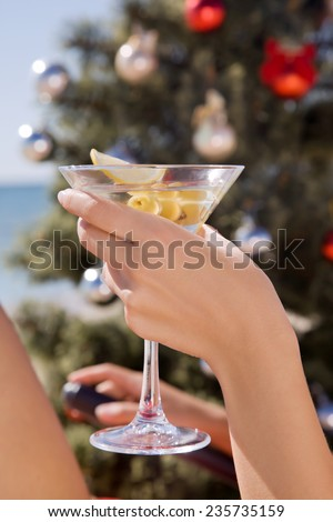 Hand with a martini glass in Christmas on the beach near the Christmas tree