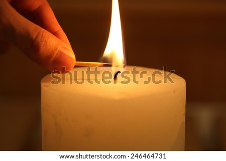 hand with a match lights a candle - stock photo