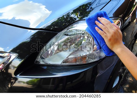 Hand with a microfiber wipe the car polishing. - stock photo