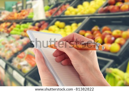 Hand with a pen writing a shopping list in supermarket  by fruit - focus on foreground - stock photo