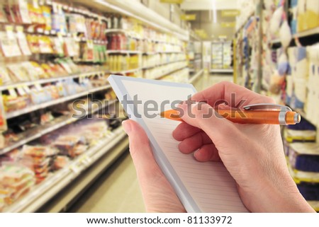 Hand with a pen writing a shopping list in supermarket - focus on foreground - stock photo