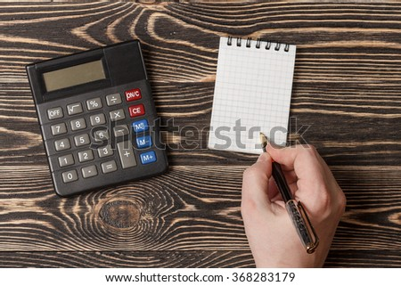hand with a pen writting blank notebook on wooden background - stock photo