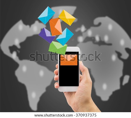 hand with a phone with many mails concept of global communication - stock photo