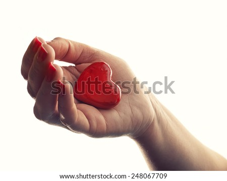 Hand with a red heart on a white background. - stock photo
