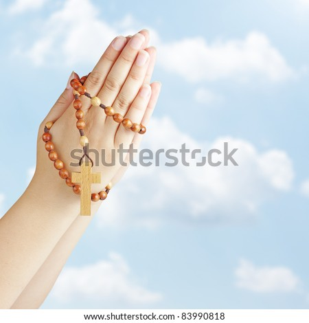 Hand with a rosary against blue sky - stock photo
