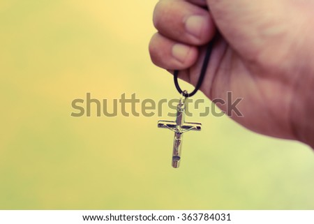 Hand with a rosary against gray background, religious concept - stock photo