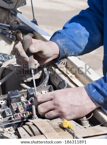 Hand with a screw-driver. Mechanic. Car repair shop.