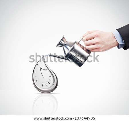 hand with a watering can and flowing clock
