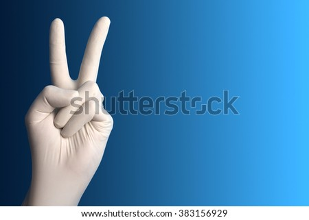 Hand with a white surgical glove showing the victory sign against a blue background