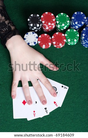 Hand with aces and poker chips