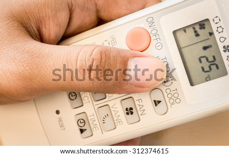 Hand with air conditioning remote control
