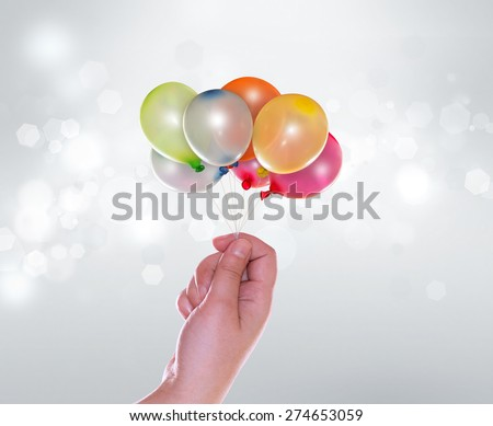 Hand with balloons on light blur background - stock photo