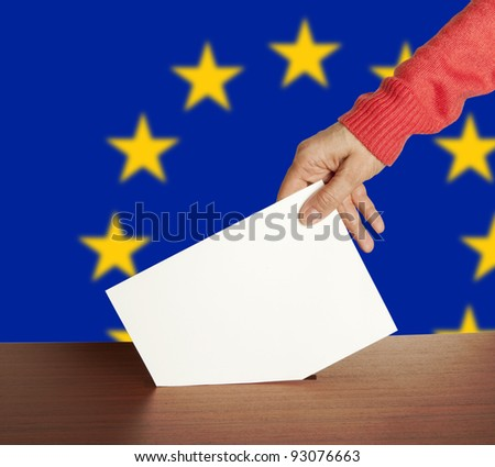 Hand with ballot and box isolated on Flag of Europe - stock photo