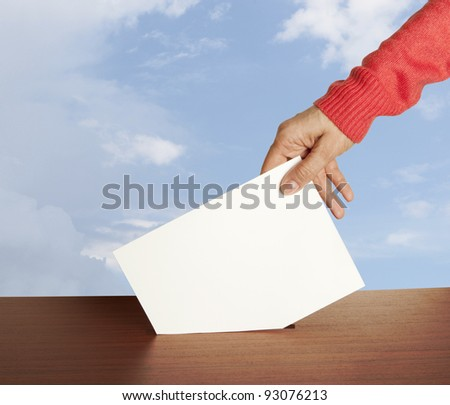Hand with ballot and box isolated on sky - stock photo