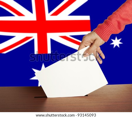 Hand with ballot and box on Flag of Australia - stock photo