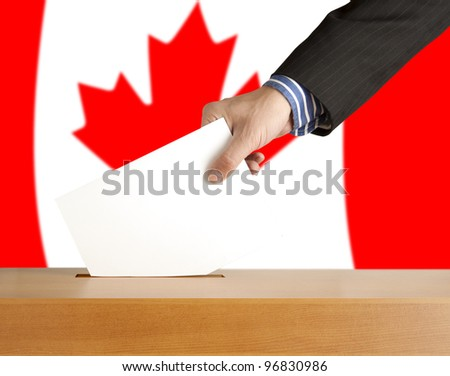 Hand with ballot and box on Flag of Canada - stock photo