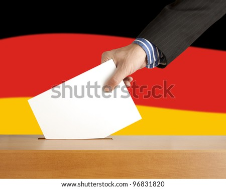 Hand with ballot and box on Flag of Germany - stock photo