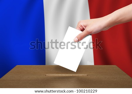 Hand with ballot and wooden box on Flag of France - stock photo