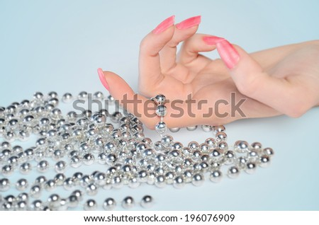 Hand with beads on table - stock photo