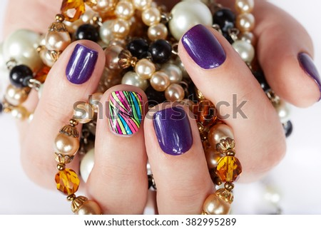 Hand with beautiful manicured nails holding pearl necklaces  - stock photo