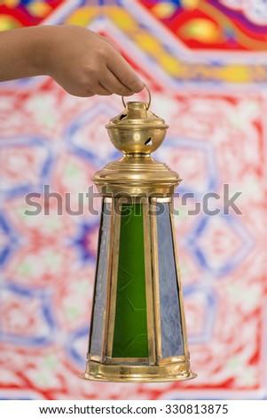 Hand with Big Ramadan Lantern over Ramadan Fabric - stock photo