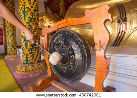 Hand with big stick hit the steel gong with background of Gold Buddha reclining in Chiang rai temple.  Famous landmark Gold Buddha in Northern of Thailand. - stock photo