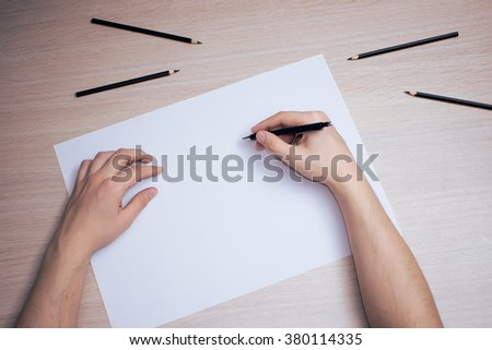 Hand with black pencil writing on white paper sheet - stock photo