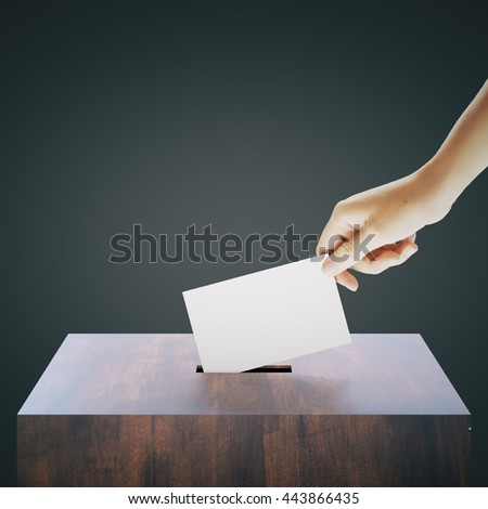 Hand with blank ballet casting vote into wooden ballot box on dark grey background. Voting concept. Mock up, 3D Rendering - stock photo