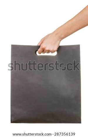 Hand with blank black paperboard bag isolated on white background - stock photo