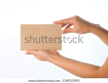 Hand with blank kraft paper envelope on white background. - stock photo