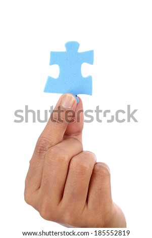 Hand with blue jigsaw puzzle isolated on white background