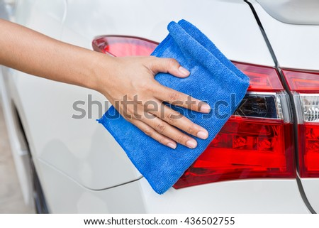 Hand with blue microfiber cloth cleaning taillight white car. - stock photo