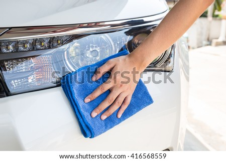 Hand with blue microfiber cloth cleaning white car. - stock photo