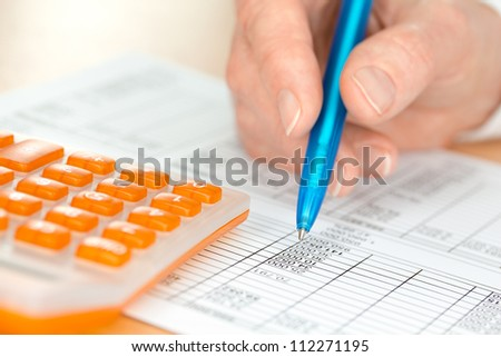 Hand with Blue Pen Checking Numbers by Orange Calculator - stock photo