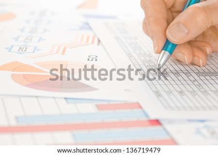Hand with Blue Pen working on Spreadsheet and Graphs  - stock photo