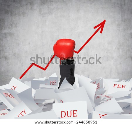 hand with boxing glove in papers heap holding red arrow - stock photo