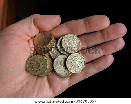 Hand with British Pound coins currency of the United Kingdom - stock photo