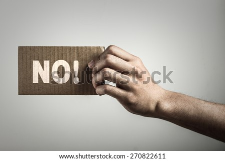 Hand with brown card is showing no with gray background. - stock photo