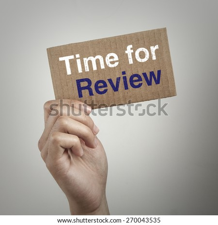 Hand with brown card is showing Time for review with gray background.