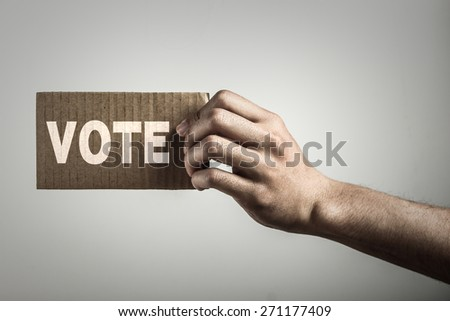 Hand with brown card is showing vote with gray background. - stock photo