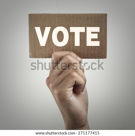 Hand with brown card is showing vote with gray gradually varied background. - stock photo