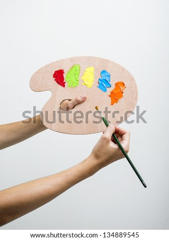 Hand with brush and paints on palette - stock photo