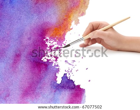 hand with brush and watercolor paint - stock photo
