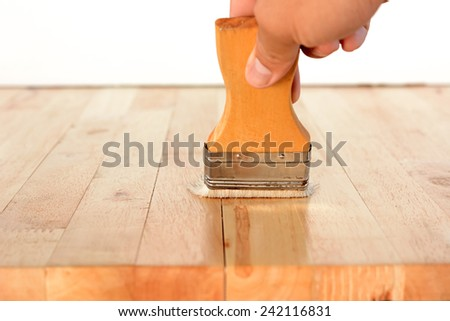 Hand with brush on wood table top - stock photo