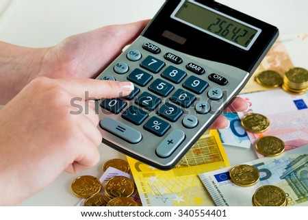 hand with calculator and bills. symbolic photo for sales, profits, taxes, and costing - stock photo