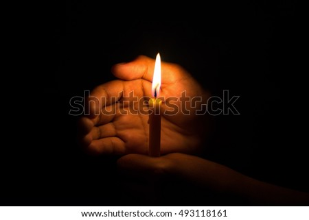 hand with candle in dark background
