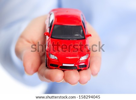 Hand with car. Auto dealership and rental concept background. - stock photo