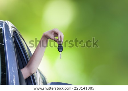 hand with car keys out the window, travel  - stock photo