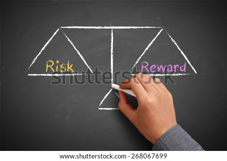 Hand with chalk is drawing Risk and reward balance scale on the chalkboard. - stock photo